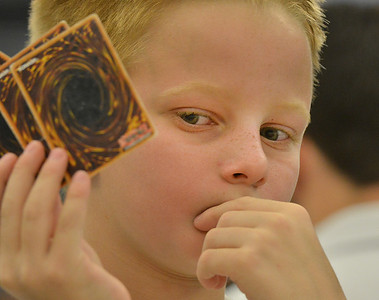 Kevin Peacock, 10, studies his cards during the Yu-Gi-Ho! tournament at the Mamie Doud Eisenhower Public Library on Friday. August 10, 2012 staff photo/ David R. Jennings