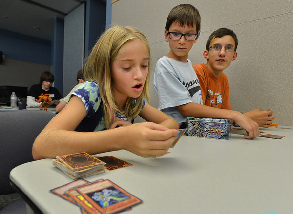 Sydney Patrick, 11, left, reads a card for her next move while brothers Peter Cabrera, 10 and Tomas , 15, watch  during the Yu-Gi-Ho! tournament at the Mamie Doud Eisenhower Public Library on Friday.<br /> August 10, 2012<br /> staff photo/ David R. Jennings
