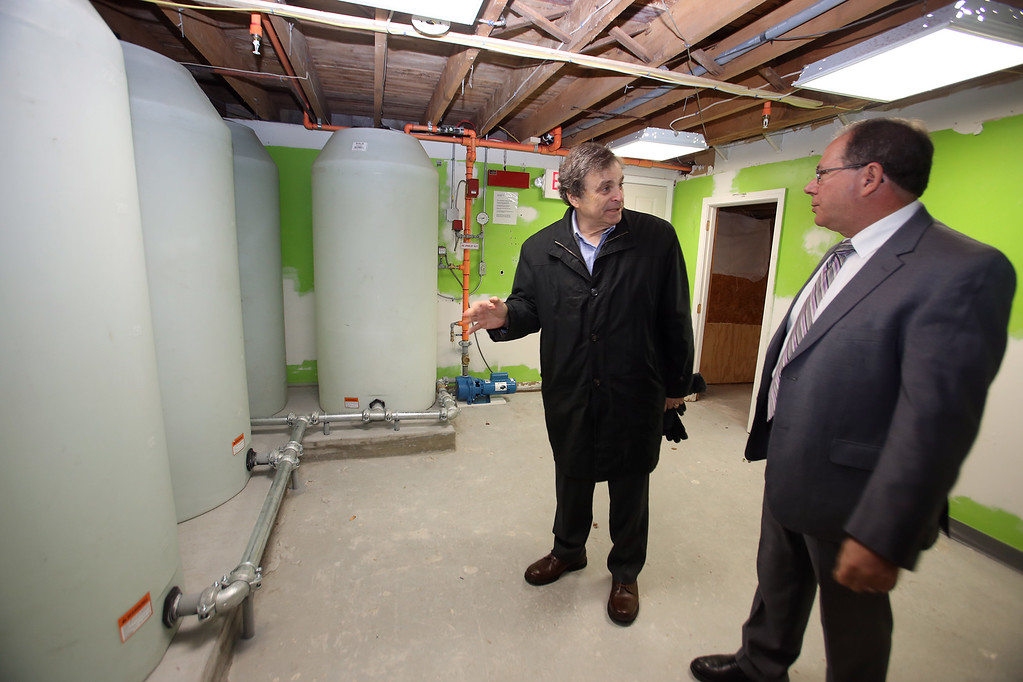 . Zack\'s House at 221 Pawtucket Blvd, a partnership between Zack\'s Team Foundation and Lowell House, will open this week as a \'sober house\' for 18-26-year-old men recovering from addiction. Bill Garr of Walpole, executive director of Lowell House, center, shows Jon Kurland, chair of the Board of Directors of Lowell House, the four 300-gallon water tanks that are part of of very high capacity sprinkler system. (SUN/Julia Malakie)