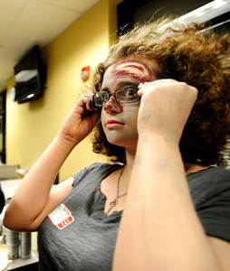 Centaurus High School freshman Liliana Benzel puts on her glasses after applying fake blood to them during the filming of an Awareness Drive week zombie video on Tuesday, Feb. 19, at Fairview High School in Boulder. The event was part of a video to bring awareness to problems such as substance abuse, cutting, stress, depression and eating disorders. For more photos and video of the zombie invasion at Fairview High School go to www.dailycamera.com DAILY CAMERA/ JESSICA CUNEO.