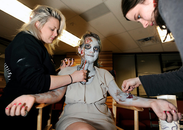 "Theatrical Costumes Ect. employees Danica Minor, left, and Kristy Pike, at right, apply makeup to Fairview High School freshman Philippa Keosheyan during the filming of an Awareness Drive week zombie video on Tuesday, Feb. 19, at Fairview High School in Boulder. The event was part of a video to bring awareness to problems such as substance abuse, cutting, stress, depression and eating disorders. For more photos and video of the zombie invasion at Fairview High School go to  <a href=""http://www.dailycamera.com"">http://www.dailycamera.com</a><br /> Jeremy Papasso/ Camera"