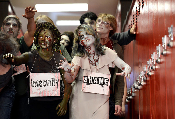 "Fairview High School freshman Philippa Keosheyan, right, and Sydney McViker, left, walk down the hall acting like zombies during the filming of an Awareness Drive week zombie video on Tuesday, Feb. 19, at Fairview High School in Boulder. The event was part of a video to bring awareness to problems such as substance abuse, cutting, stress, depression and eating disorders. For more photos and video of the zombie invasion at Fairview High School go to  <a href=""http://www.dailycamera.com"">http://www.dailycamera.com</a><br /> Jeremy Papasso/ Camera"
