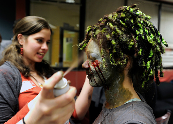 """Theatrical Costumes Ect. employees Kristy Pike, left, and Danica Minor, at center, apply makeup to Fairview High School freshman Sydney McViker during the filming of an Awareness Drive week zombie video on Tuesday, Feb. 19, at Fairview High School in Boulder. The event was part of a video to bring awareness to problems such as substance abuse, cutting, stress, depression and eating disorders. For more photos and video of the zombie invasion at Fairview High School go to  <a href=""""http://www.dailycamera.com"""">http://www.dailycamera.com</a><br /> Jeremy Papasso/ Camera"""