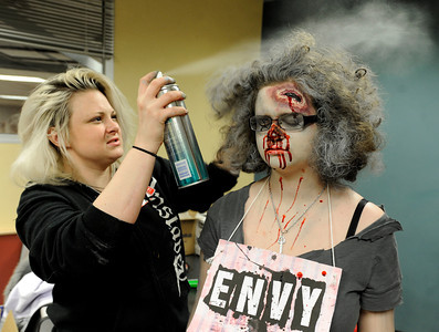 Theatrical Costumes Ect. employee Danica Minor sprays a silver substance into the hair of Centaurus High School freshman Liliana Benzel during the filming of an Awareness Drive week zombie video on Tuesday, Feb. 19, at Fairview High School in Boulder. The event was part of a video to bring awareness to problems such as substance abuse, cutting, stress, depression and eating disorders. For more photos and video of the zombie invasion at Fairview High School go to www.dailycamera.com Jeremy Papasso/ Camera