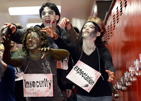 "Fairview High School freshman Sydney McViker, left, sophomore Rodrigo Guadarrana, center, and senior Mia Farago-Iwamasa act like zombies as they walk down the hall during the filming of an Awareness Drive week zombie video on Tuesday, Feb. 19, at Fairview High School in Boulder. The event was part of a video to bring awareness to problems such as substance abuse, cutting, stress, depression and eating disorders. For more photos and video of the zombie invasion at Fairview High School go to  <a href=""http://www.dailycamera.com"">http://www.dailycamera.com</a><br /> Jeremy Papasso/ Camera"