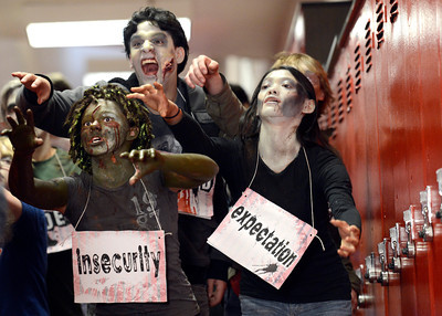 Fairview High School freshman Sydney McViker, left, sophomore Rodrigo Guadarrana, center, and senior Mia Farago-Iwamasa act like zombies as they walk down the hall during the filming of an Awareness Drive week zombie video on Tuesday, Feb. 19, at Fairview High School in Boulder. The event was part of a video to bring awareness to problems such as substance abuse, cutting, stress, depression and eating disorders. For more photos and video of the zombie invasion at Fairview High School go to www.dailycamera.com Jeremy Papasso/ Camera