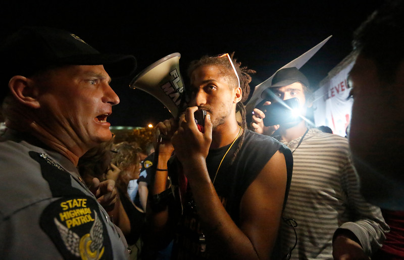 A protester speaks into a microphone as an Ohio State Highway Patrol officer monitors a line of protesters gathering outside the Republican National Convention in Cleveland, Ohio on July 21, 2016.
