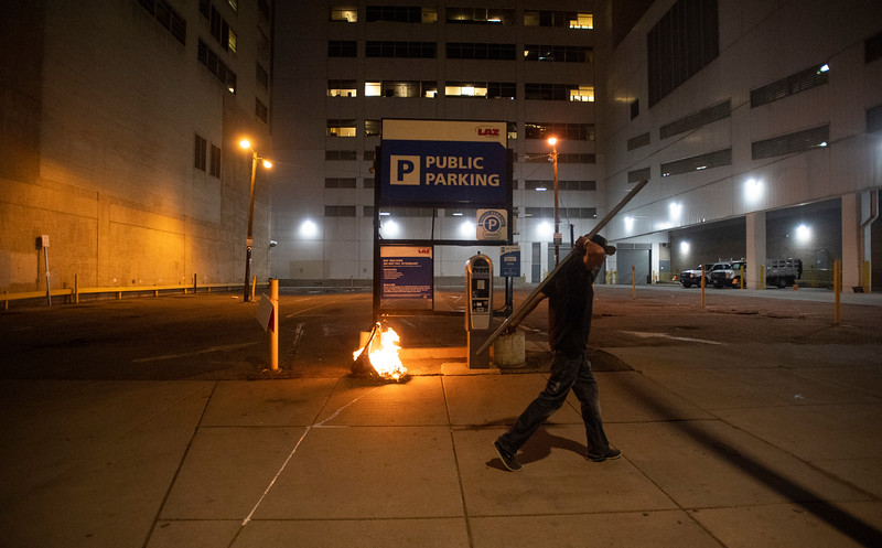 A protester carries a pipe down a sidewalk beside the remains of a burning tire during a protest in response to the police killing of George Floyd, an unarmed black man in Minneapolis, in Denver, Colo. on Friday, May 29, 2020.