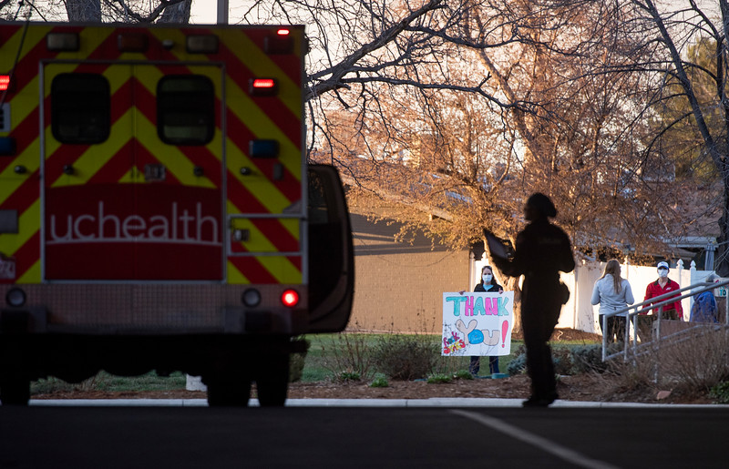 People hold signs thanking health care workers outside the ambulance bay at UCHealth Poudre Valley Hospital during the coronavirus pandemic in Fort Collins, Colo. on Friday, March 10, 2020.