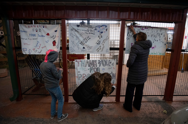 Students from Loveland Classical Schools hang signs thanking firefighters battling nearby blazes such as the Cameron Peak Fire and East Troublesome Fire at The Dam Store along U.S. Highway 34 near Loveland, Colo. on Thursday, Oct. 22, 2020.