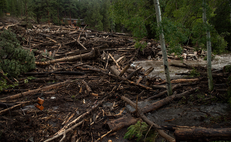 A debris field clogs the Cache La Poudre River after flash flooding ripped through a drainage near Black Hollow Road in the Poudre Canyon near Rustic, Colo. on Wednesday, July 21, 2021.
