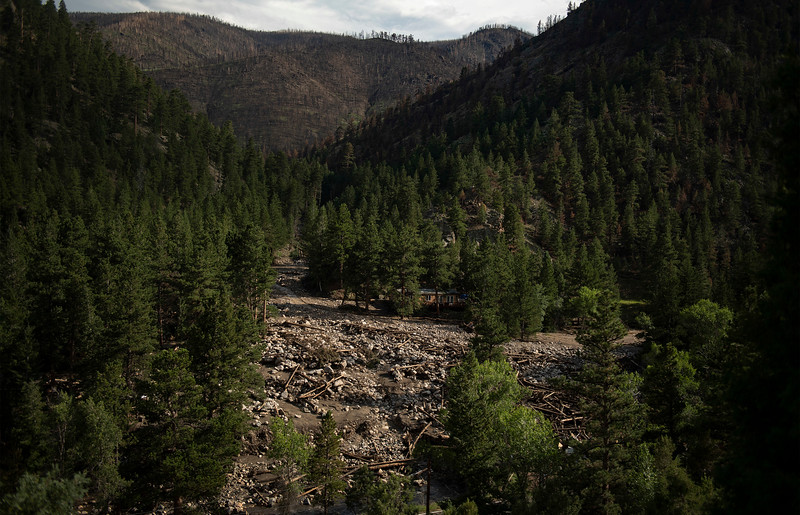 A debris field stretches along the banks of the Cache La Poudre River after flash flooding ripped through a drainage near Black Hollow Road in the Poudre Canyon near Rustic, Colo. on Wednesday, July 21, 2021.