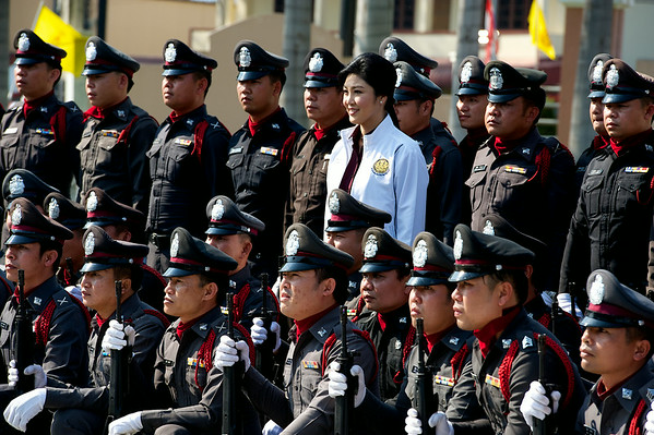 Former Prime Minister Yingluck Shinawatra poses for photos with local security personnel.