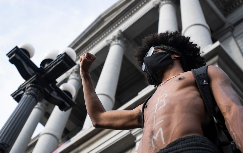 Kellian Conway, of Denver, raises his arm as he stands in front of the Colorado Capitol during the fifth night of protests in response to the police killing of George Floyd, an unarmed black man in Minneapolis, in Denver, Colo. on Monday, June 1, 2020.