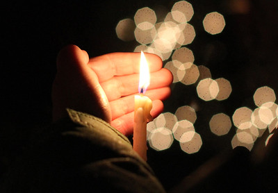 Newly lit Christmas tree lights shine behind a candle during the tree lighting ceremony at Meetinghouse Square in Fallsington on Sunday evening. Community members joined the Fallsington United Methodist Church Worship Choir Christmas carols as the tree was lit.