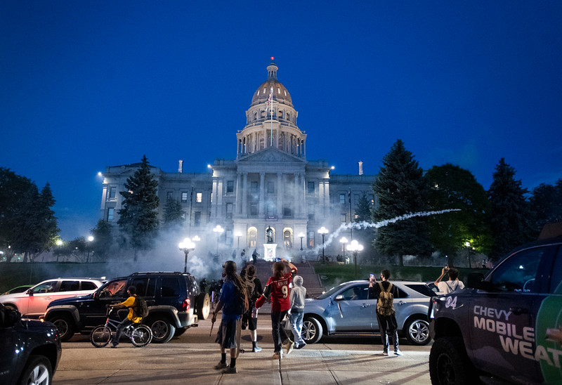 Law enforcement shoots tear gas into the crowd in front of the Colorado Capitol during a protest in response to the police killing of George Floyd, an unarmed black man in Minneapolis, in Denver, Colo. on Friday, May 29, 2020.