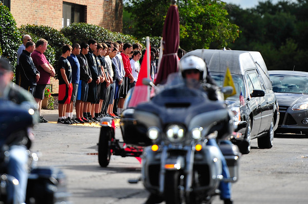 The Richards High School football team stands in silence as the casket of Steven Smith drives by the school in route to Our Lady of the Ridge church. Steven Smith, who attended Richards High School and played for the Bulldog football team, was killed in a head-on collision. Saturday, September 19th, 2015, in Chicago Ridge. (Gary Middendorf-Daily Southtown)
