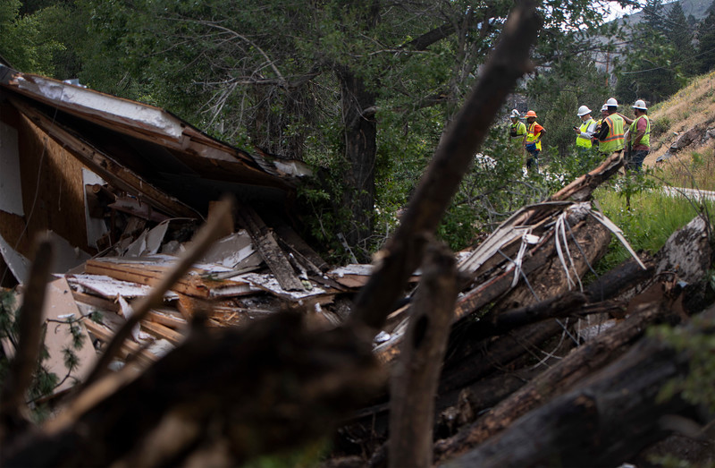 Contractors assess the damage of a debris field clogging the Cache La Poudre River after Tuesday's flash flooding ripped through a drainage near Black Hollow Road in the Poudre Canyon near Rustic, Colo. on Wednesday, July 21, 2021.