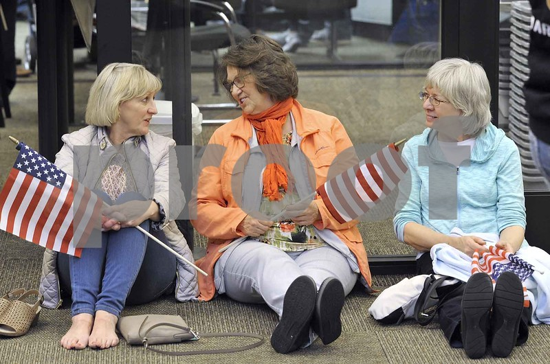 -Messenger photo by Hans Madsen<br /> <br /> Judy Zeidler, of Davenport, at left, Lorraine Tilton, of St. Ansgar and Sonnie Tharp, of Milo, found a comfortable spot on the floor to wait for the arrival of the Brush Creek Area Honor Flight Saturday night at the Fort Dodge Regional Airport. The friends were waiting for Army veteran Ken Tilton.