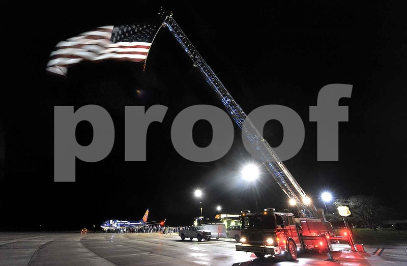 -Messenger photo by Hans Madsen<br /> <br /> With the Fort Dodge Fire Department's Ladder 1 truck flying the U.S. Flag, the 16th Brushy Creek Area Honor Flight returns to the Fort Dodge Regional Airport Saturday night from its day long trip to Washington D.C.