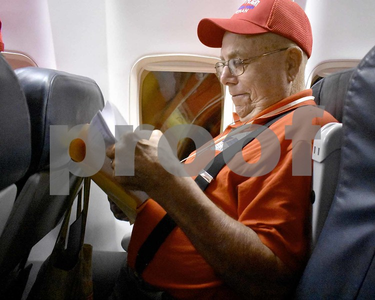 -Messenger photo by Chad Thompson <br> Russ Mohr, of Fort Dodge, a U.S. Navy veteran, opens an envelope full of letters on the flight back home. Mohr said he has 24 grandchildren.