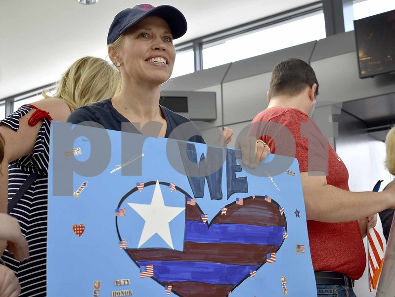 -Messenger photo by Chad Thompson <br> Kelly Breedlode, of Vienna, Virginia, holds up a sign welcoming veterans at Dulles International Airport in Washington, D.C., Saturday.