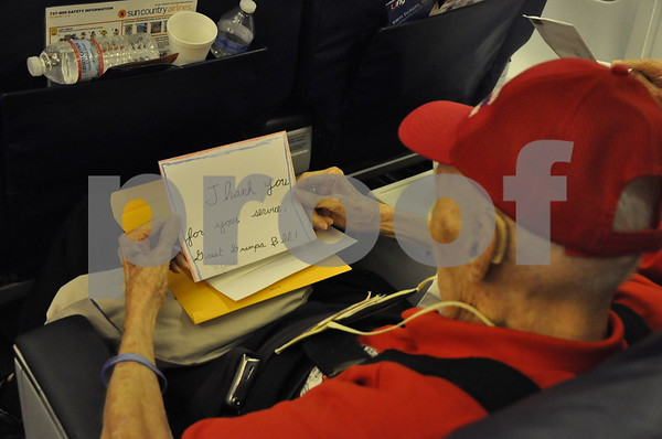 """-Messenger photo by Joe Sutter<br /> <br /> World War II veteran Bill Lees opens a card that says """"Thank you for your service, Great Grandpa Bill."""" The 98 veterans on the honor flight received notes from their families during mail call on the flight home."""