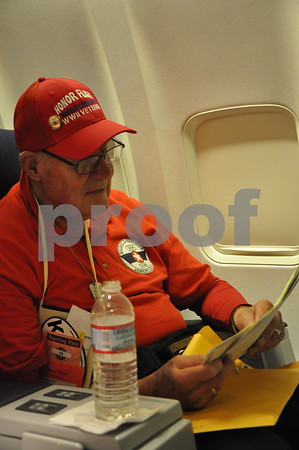 -Messenger photo by Joe Sutter<br /> <br /> World War II veteran Lael Lesmeier opens his envelope during mail call on the flight back to Fort Dodge.