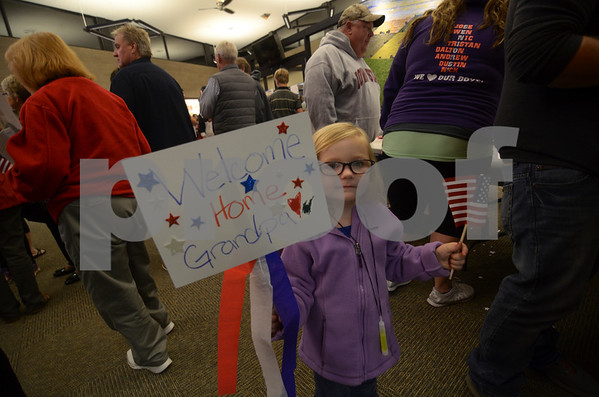 -Messenger photo by Jesse Major<br /> Bentlie Rousseau, 4, of Humboldt, holds a sign and American Flag as she waits for her great grandfather, Ron Sander, to return from the Brushy Creek Area Honor Flight on Saturday.