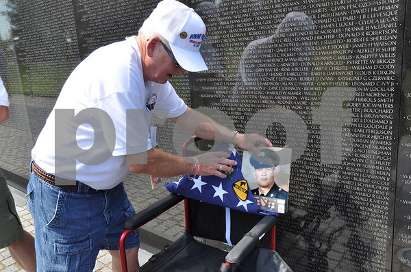 -Messenger photo by Joe Sutter<br /> <br /> Brushy Creek Area Honor Flight chairman Ron Newsum places the burial flag of Vietnam Veteran Steven Dorsey, of Callender, at the Vietnam War Memorial. Dorsey passed away in spring of 2015. A flag for Vietnam Veteran Robert Skelton, of Onawa, was also taken.