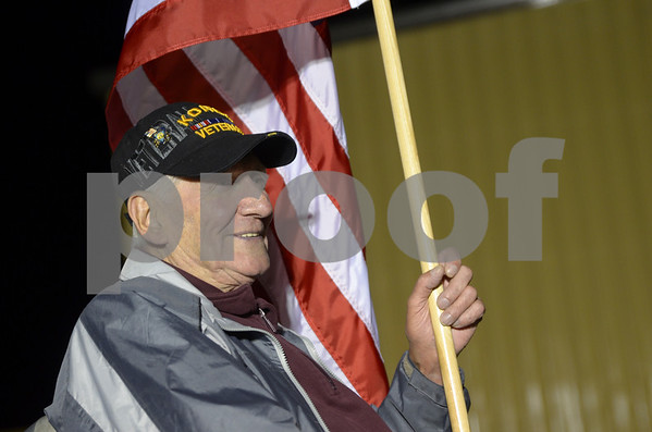 -Messenger photo by Jesse Major<br /> John Olmstead, a Korean War veteran who served in the Army, sits outside the Fort Dodge Regional Airport holding an American flag as he greets veterans going on the Brushy Creek Area Honor Flight on Saturday. Olmstead went on the flight two years ago.