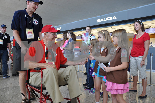 -Messenger photo by Joe Sutter<br /> <br /> Veteran Keith Chapman is greeted by girls from Girl Scout troop 81625 of Brunswick, Maryland. Boy Scouts, American Heritage Girls, and volunteers of all ages made a huge welcoming line for the Brushy Creek Area Honor Flight veterans as they arrived at Dulles Airport Saturday.