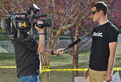 TV news reporter interviewing man at protest outside town hall meeting held by Colorado Representative Micheal Coffman.