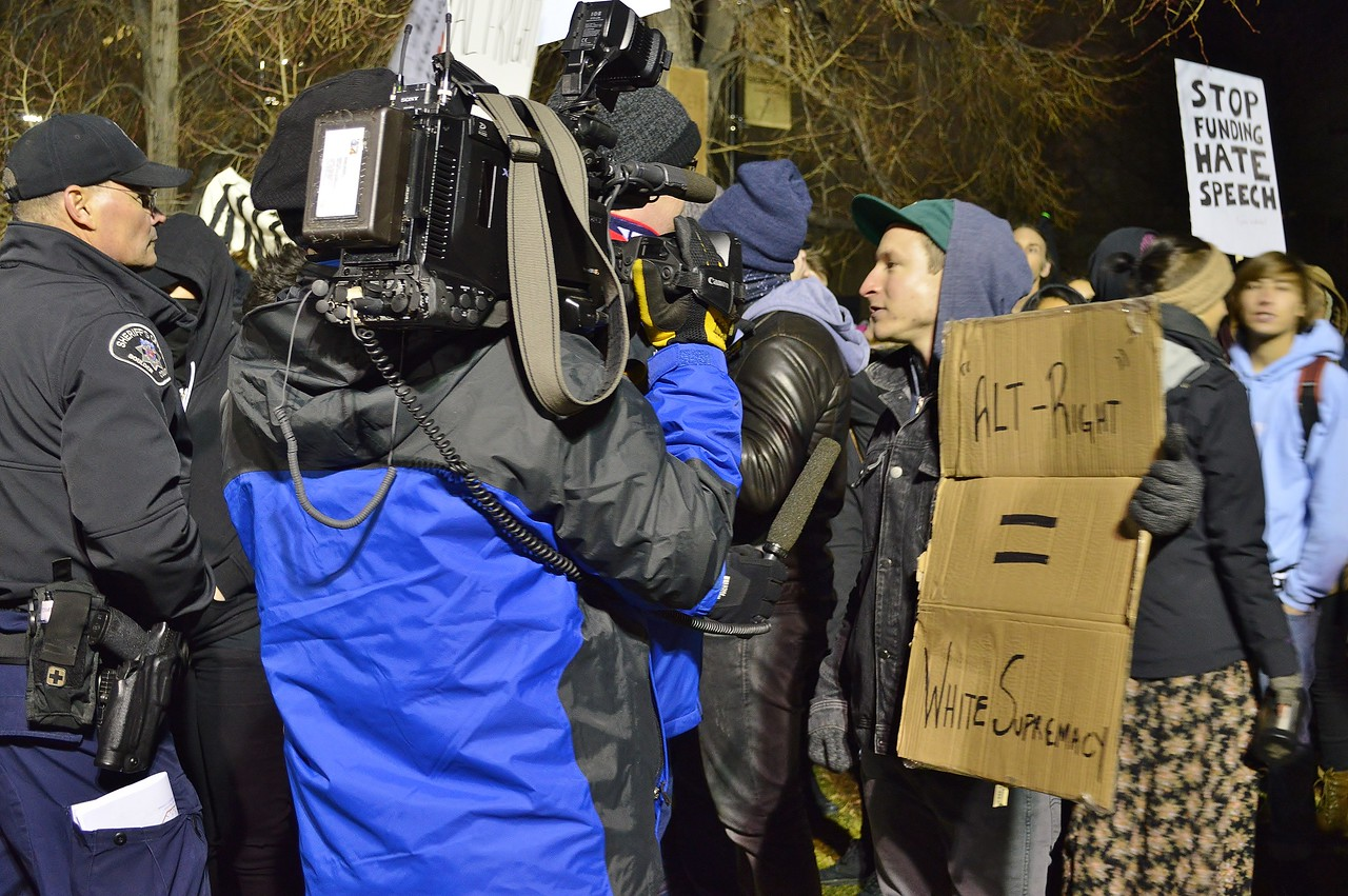 Anti Milo Yiannopoulos protester being interviewed by a TV news reporter at speech by Milo Yiannopoulos on the Univ of Colorado campus in Boulder.