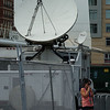 Woman takes a cigarette break, near a satellite dish, behind the scenes of the MSNBC set at the 2008 Democratic National Convention in Denver.