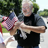 Don Knight | The Herald Bulletin<br /> Brian Engelhardt with the American Legion hands out flags to people who lined the processional route for Airman Howard Martin as he returned to Elwood on Thursday. For a gallery of photos visit photos.heraldbulletin.com.