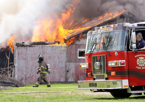 Don Knight | The Herald Bulletin<br /> Engine 7 is moved to put it's onboard nozzle at a better angle to attack a fire in a storage building at Man4Man ministries on Tuesday. An employee was burning a box spring behind the building which might have been the cause of the fire.