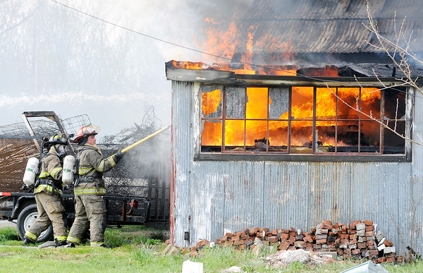 Don Knight | The Herald Bulletin<br /> Firefighters use a hook to pull away the metal siding while battling a fire in a storage building at Man4Man ministries that housed mattresses on Tuesday. No one was in the burning building, and no injuries were reported.