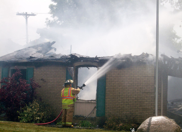 A firefighter douses the garage of a house at the corner of Laurel Lane and Central Way in Edgewood Thursday.