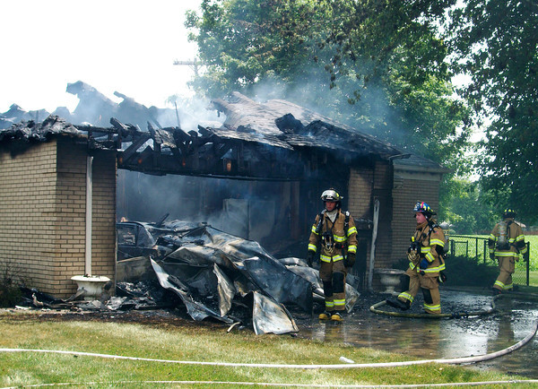 Firefighters assess damage in the garage area of a house at the corner of Laurel Lane and Central Way Thursday following a fire that left the house a total loss.