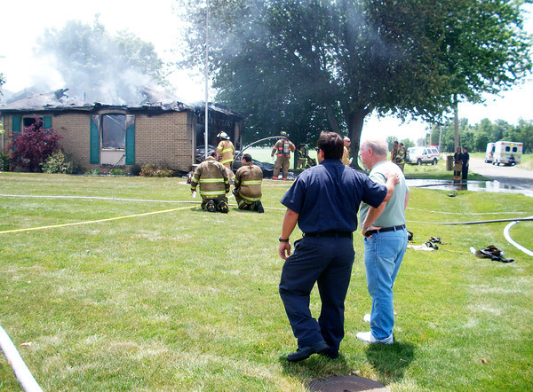 Homeowner Louis Givens, right, watches as firefighters work to extinguish a fire at his home at the corner of Laurel Lane and Central Way on Thursday.
