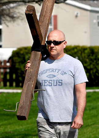 John P. Cleary | The Herald Bulletin<br /> Tim Hanshew carries a large wooden cross around Anderson neighborhoods throughout the year.