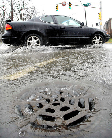 John P. Cleary | The Herald Bulletin<br /> With heavy rains falling over the area storm drains had a hard time keeping up with the large volume of water running into them causing standing water in streets like here at the intersection of Brown Street and `19th Street.