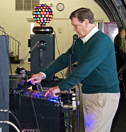 Popular local DJ Buddy Patterson operates the controls of his sound system during the Saint Patrick's Day dance at the Rangeline Community Center.