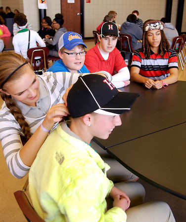 """John P. Cleary   The Herald Bulletin<br /> Highland Middle School students held """"Hat Day"""" Friday to raise money for classmate Suncerria Uditsky who was killed in a bicycle accident.  Here Alexa Nadaline, left, helps adjust the hat for Dakotah Alumbaugh, foreground, as other students Mason Barnett, Colton Brooks, and Patrick Sawyer look on.  Students paid two dollars to be able to wear a hat to school Friday with the money raised going to Uditsky's family.  <br /> To view or buy this photo and other Herald Bulletin photos, visit<br /> heraldbulletin.smugmug.com."""