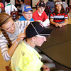 "John P. Cleary | The Herald Bulletin<br /> Highland Middle School students held ""Hat Day"" Friday to raise money for classmate Suncerria Uditsky who was killed in a bicycle accident.  Here Alexa Nadaline, left, helps adjust the hat for Dakotah Alumbaugh, foreground, as other students Mason Barnett, Colton Brooks, and Patrick Sawyer look on.  Students paid two dollars to be able to wear a hat to school Friday with the money raised going to Uditsky's family.  <br /> To view or buy this photo and other Herald Bulletin photos, visit<br /> heraldbulletin.smugmug.com."