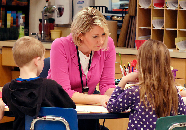 John P. Cleary | The Herald Bulletin<br /> Alexandria-Monroe Elementary School first grade teacher Kimberly Osterhoff works with her students Monday on their first day back in the classroom from spring break.