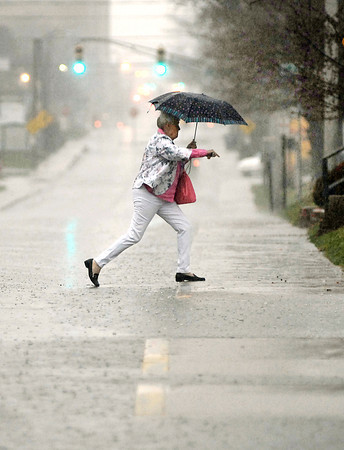 John P. Cleary | The Herald Bulletin<br /> With heavy rains falling over the area standing water became a problem for both motorists and pedestrians alike.  Here this lady steps over the large stream of water running down the curb in the 2000 block of Jackson Street near St. Vincent Regional Hospital Thursday.