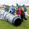 Don Knight | The Herald Bulletin<br /> Pendleton Heights baseball team rolls their infield tarp off the field on Friday. Despite the tarp large puddles of water formed on the infield postponing Friday's doubleheader against Greenfield-Central to today.