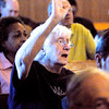 "John P. Cleary | The Herald Bulletin<br /> Phyllis Ford of Southdale Church of the Nazarene raises her hand in praise as she sings along  to ""Old Rugged Cross"" during the annual Community Good Friday Worship Service at Friendship Missionary Baptist Church."